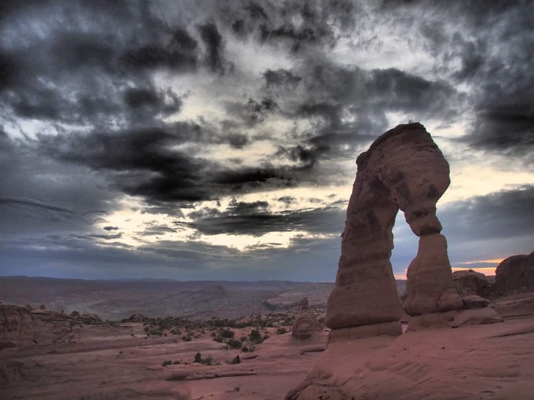 Storm Clouds Hover Over One Of The Natural Stone Formations In Arches N.p. Utah.