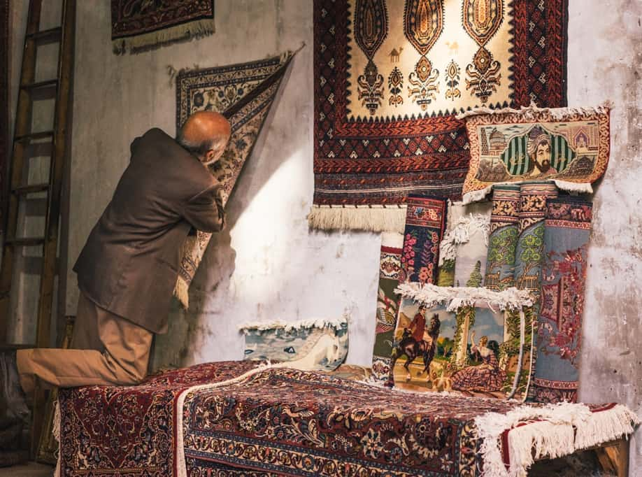 Man Going Through His Carpets At The Market