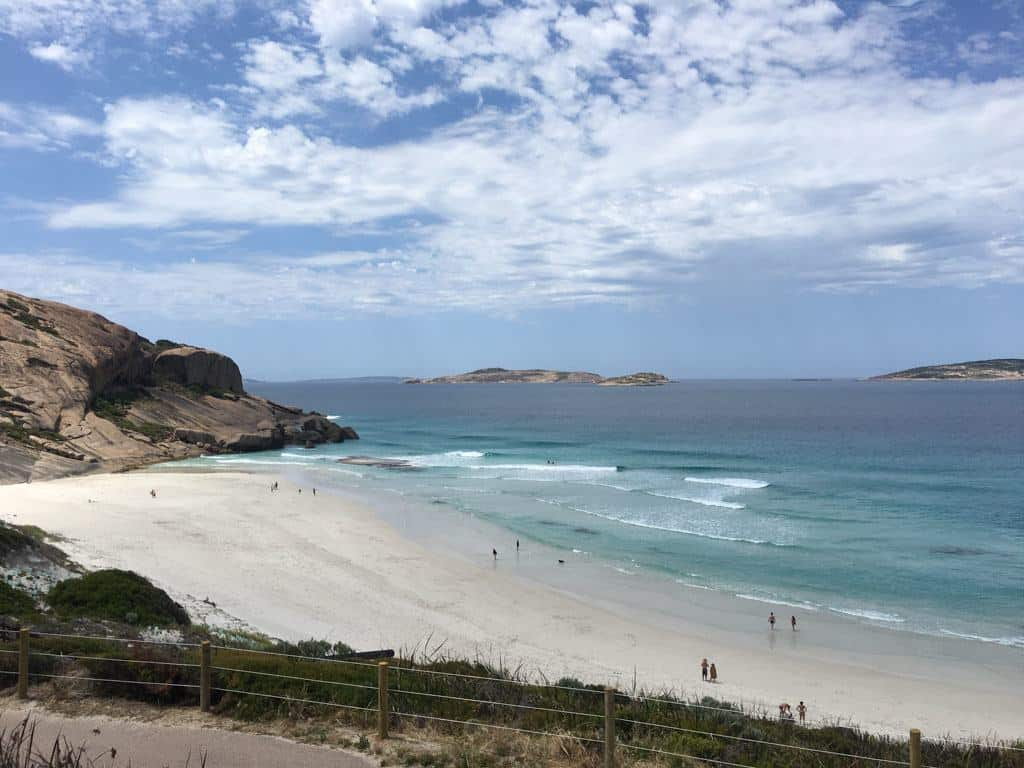 White Sand Beach With Waves And Surfers Out On The Water