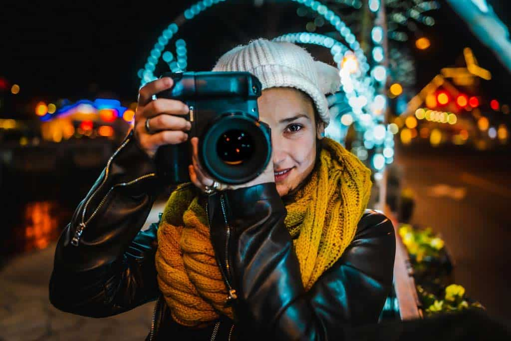 Details Girl Holding Camera With Lights In Background